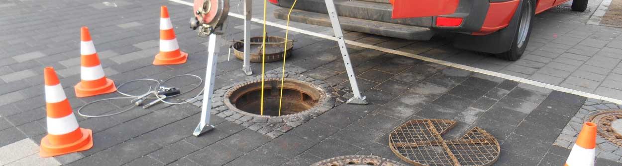 Kanalsanierung - offener Kanalschacht abgesperrt mit Pylonen