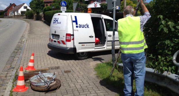 Firmenwagen IB-Hauck mit Arbeiter und offenem Kanaldeckel